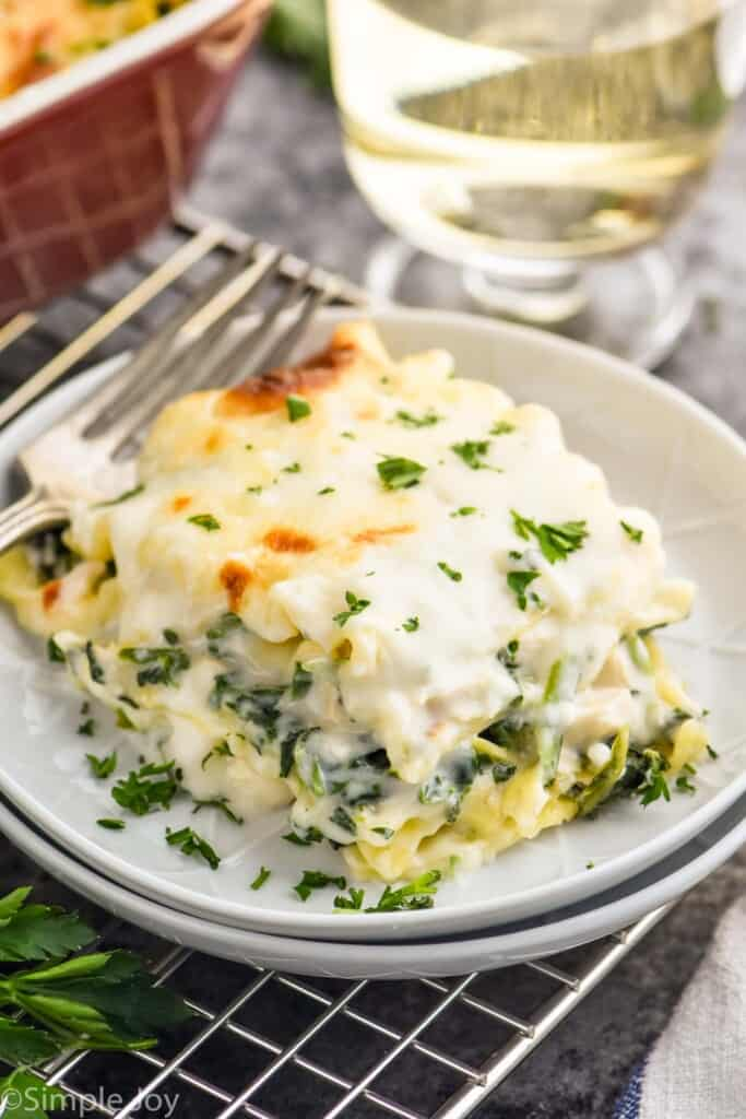 a piece of chicken lasagna recipe on two white plates