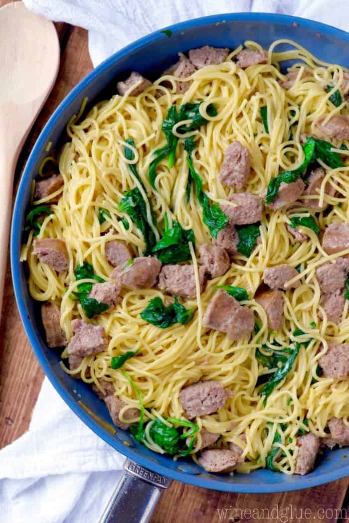 In a blue pot, the One Pot Creamy Spaghetti and Sausage is made with long spaghetti noodles, sausages, and spinach.