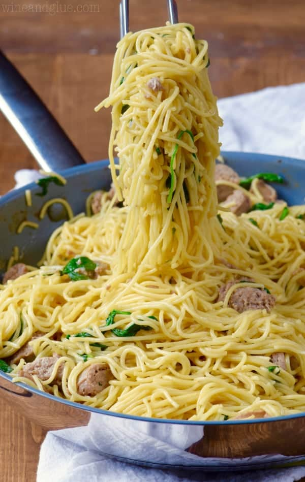 In a sauce pan, the One Pot Creamy Spaghetti and Sausage is picked up by a pair of tongs.