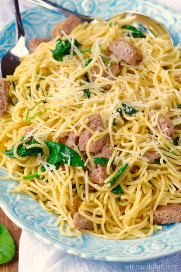 On a white plate, the One Pot Creamy Spaghetti Sausage has halved sausage slices and sautéed spinach topped with parmesan cheese.