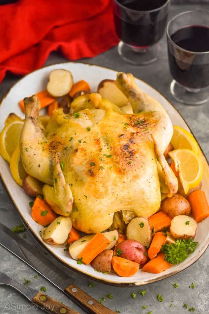 slow cooker whole chicken on a white platter surrounded by vegetables