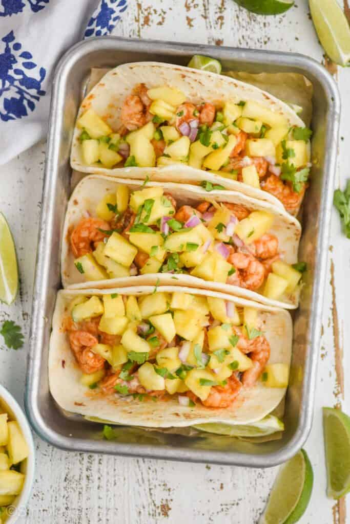 overhead view of three shrimp tacos on a rimed small metal baking sheet, topped with pineapple salsa with lime wedges on the white wood surface around them