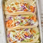 overhead view of three shrimp tacos in corn tortillas garnished with cilantro cream and green and red cabbage on a small baking tray with lime wedges around them