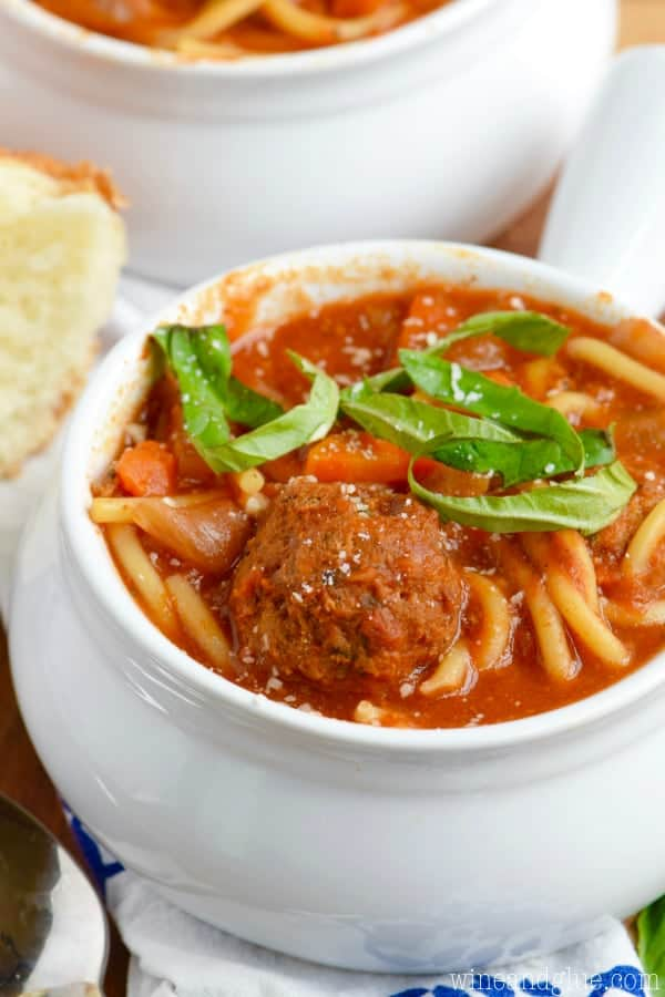 In a white bowl, the Slow Cooker Spaghetti and Meatball Soup is topped with sliced basil.