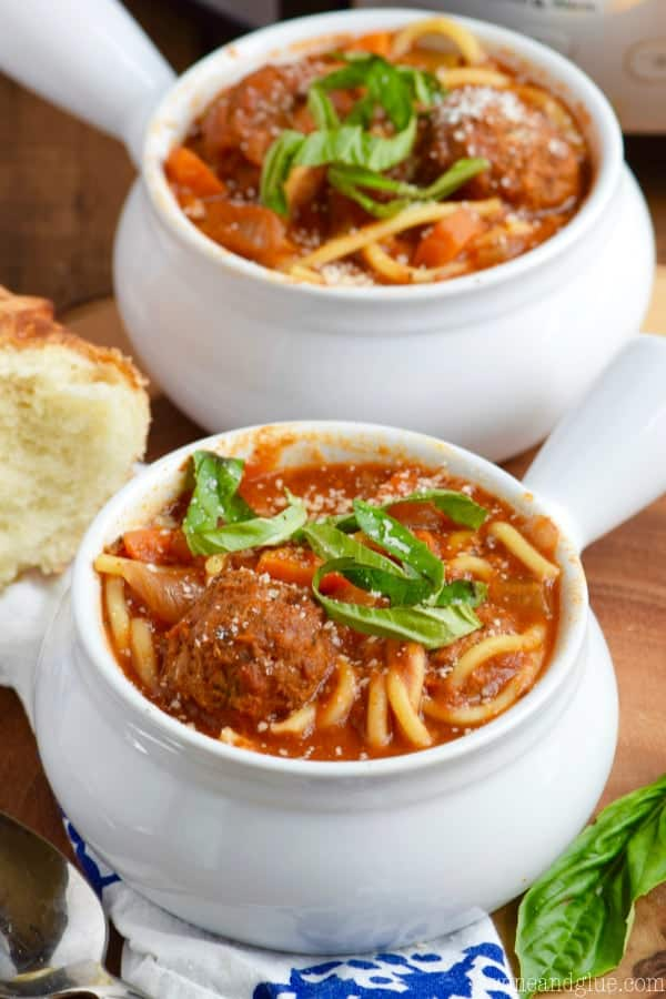 In a small white bowl, the Slow Cooker Spaghetti and Meatball Soup is topped with some cheese and basil.