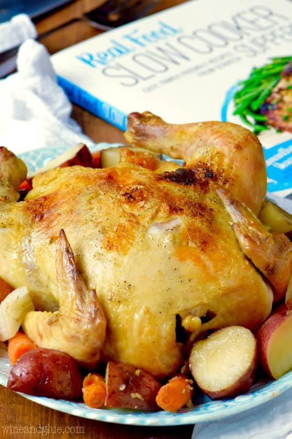On a blue plate, a golden brown whole chicken is surrounded by potatoes and carrots.