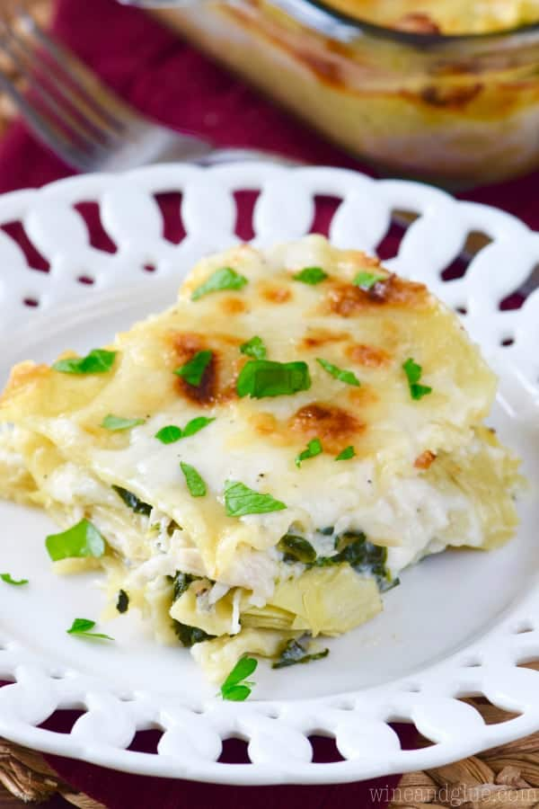 On a white plate, the Spinach Artichoke Lasagna has a crisp layer of cheese and topped with basil.