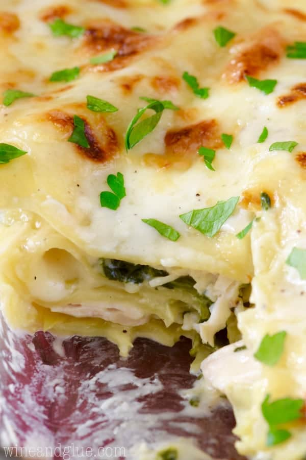 A little scoopful of the Spinach Artichoke Lasagna is taken out showing the creamy interior with spinach, artichoke, and chicken.