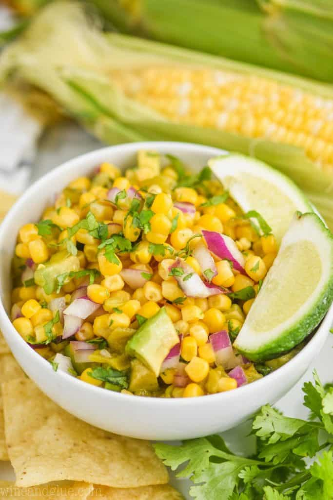 small white bowl filled with corn salsa recipe and garnished with lime wedges, whole corn on the cob in the background