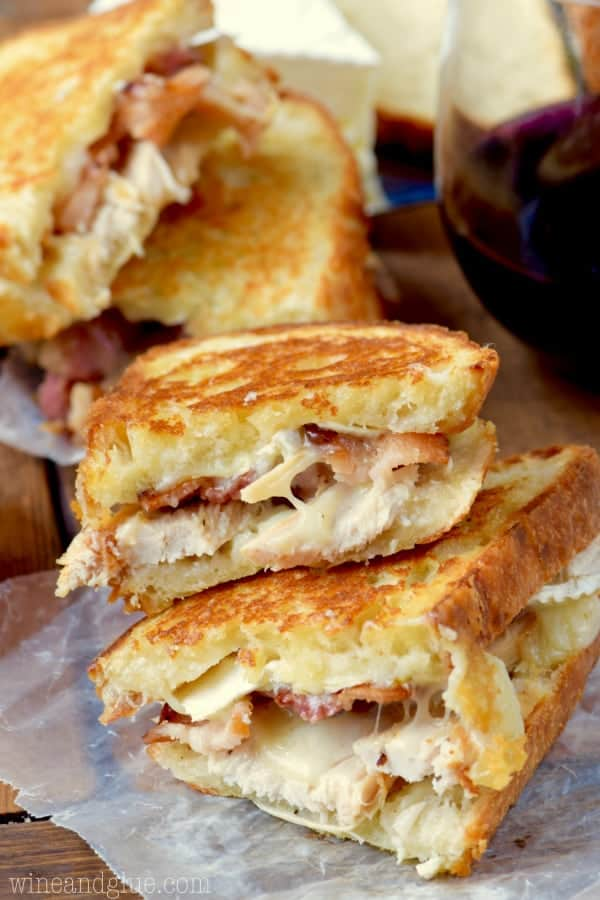 A stack of the Turkey Bacon Brie Grilled Cheese Sandwich are cut in half showing the melted gooey center.