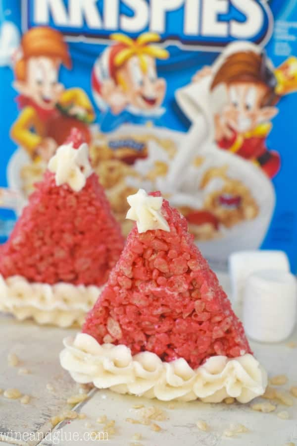 In front of the Rice Krispies cereal box, the Rice Krispies Santa Hat is red with white frosting piped on the tip and at the bottom.
