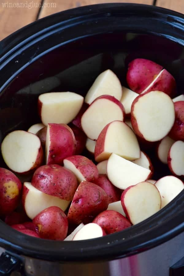 Sliced up red potatoes fill up the crock pot.