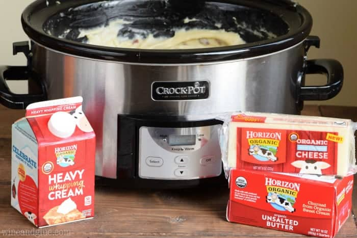 Horizon's Organic Heavy cream, butter, and cheese is in front of the crockpot filled with the mashed potatoes.