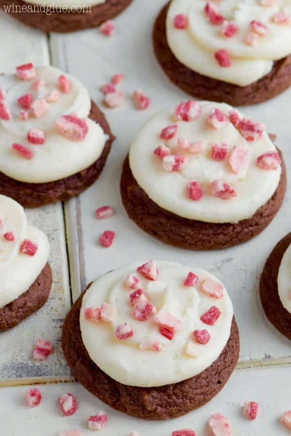 On a white counter the Chocolate Peppermint Cake Mix Cookies have white frosting sprinkled with broken pieces of peppermint.