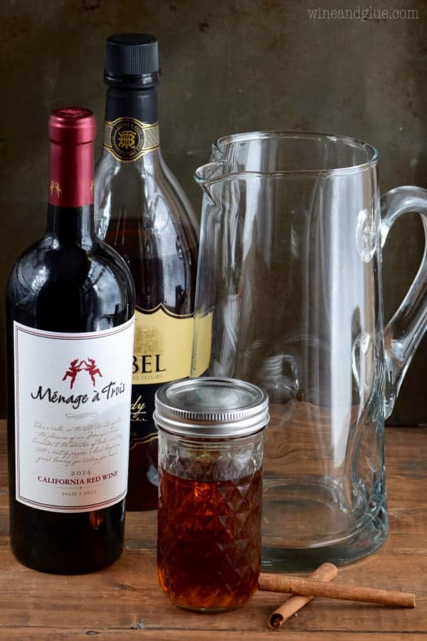 The ingredients of the Cinnamon Sangria is next to a pitcher. (Red wine, honey, cinnamon sticks, and brandy)