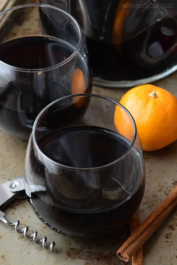 In a whine glass, the Cinnamon Sangria has an almost black color and surrounded by cinnamon sticks and oranges.
