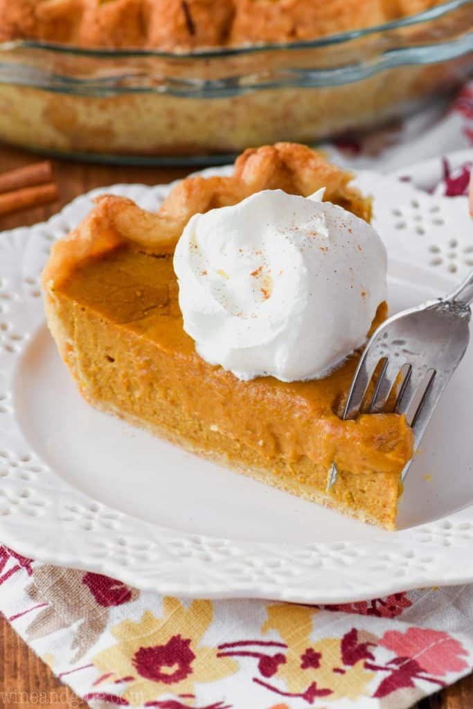 fork digging into a slice of the best pumpkin pie with a dollop of whipped cream