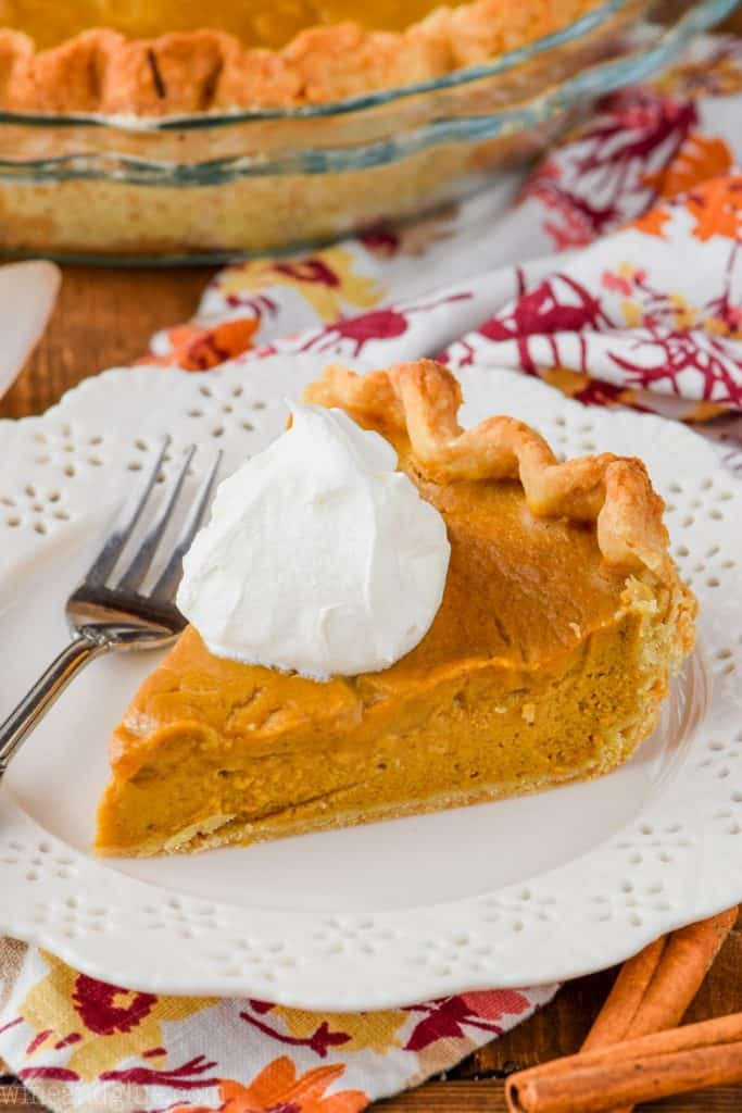 slice of the best pumpkin pie from scratch on a plate with whipped cream