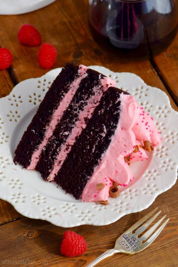 The Red Wine Chocolate cake has three layers with pink frosting in between and topped with pink frosting, pink sprinkles, and shaved chocolate.