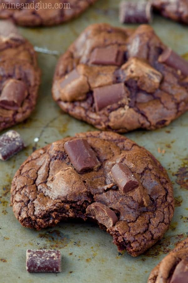 On a baking pan, the Triple Chocolate Chunk Cookie has a little bite showing the moist interior.