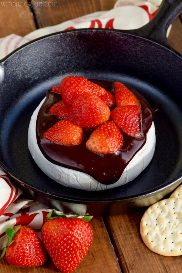 In a cast iron, the brie cheese is covered with melted chocolate and cut strawberries.