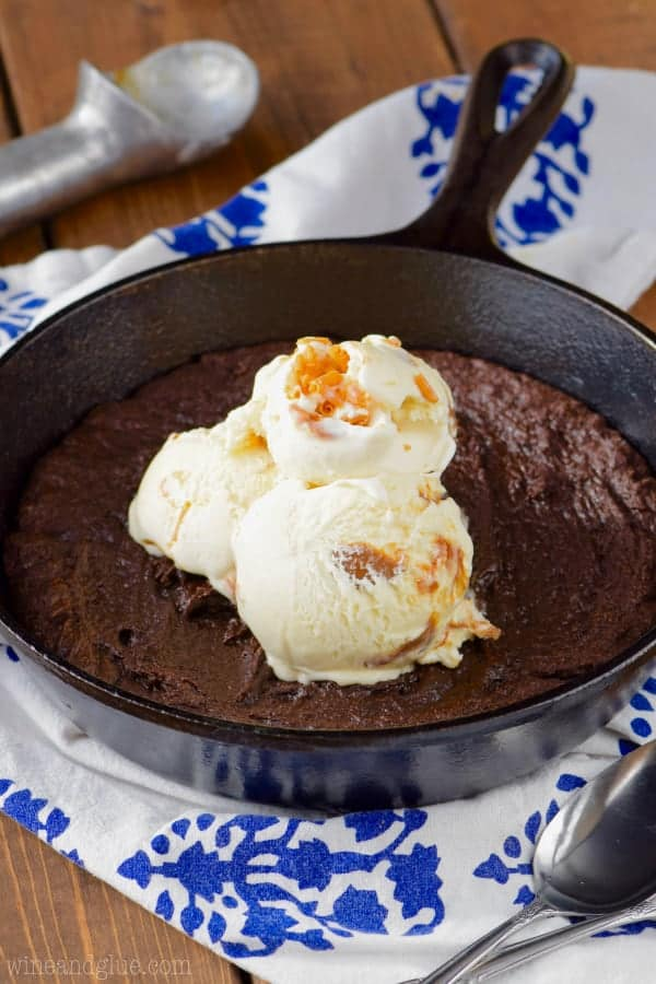 In a cast iron skillet, the Skillet Brownie is fully cooked topped with three caramel gelato scoops.
