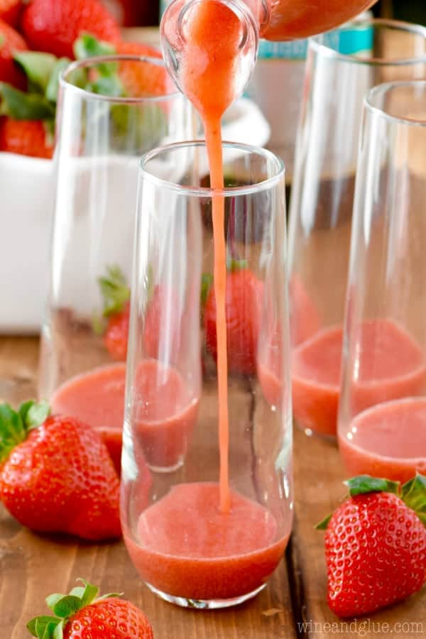 In the champagne glass, the strawberry syrup is being poured for the Strawberry Bellinis.