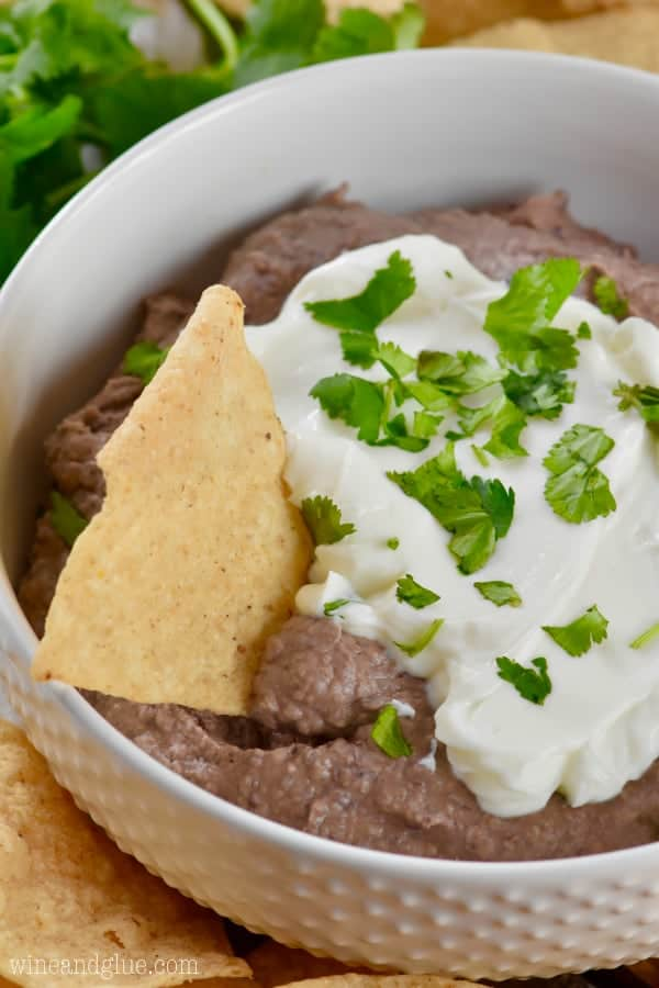 a tortilla chip being dipped into the black bean dip in a white bowl with sour cream and cilantro