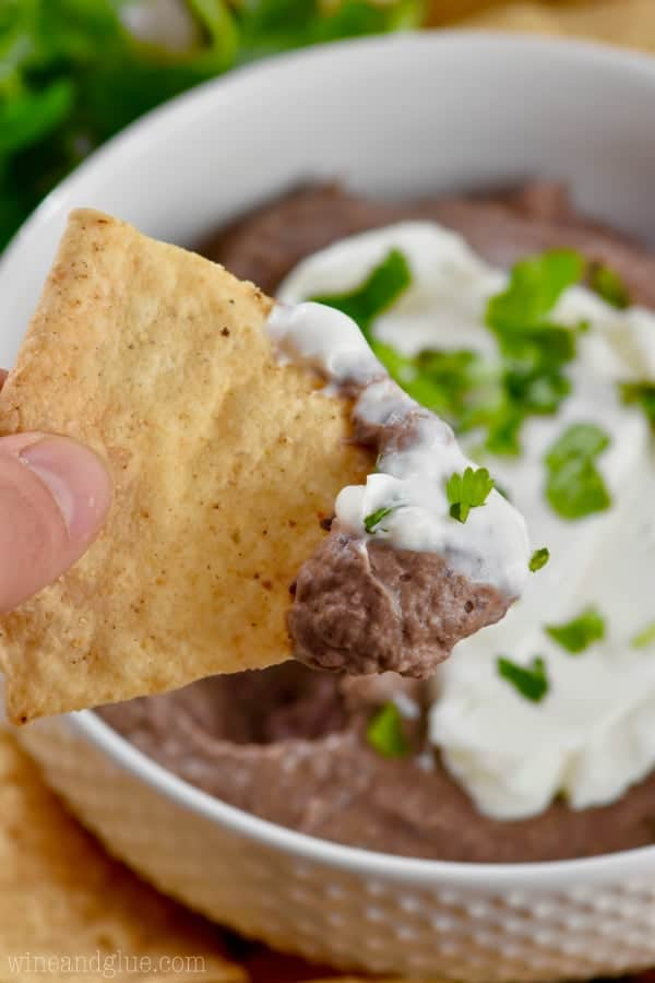 On the tip of the chip, half of the tip has the Black Bean Dip and the other half is sour cream.