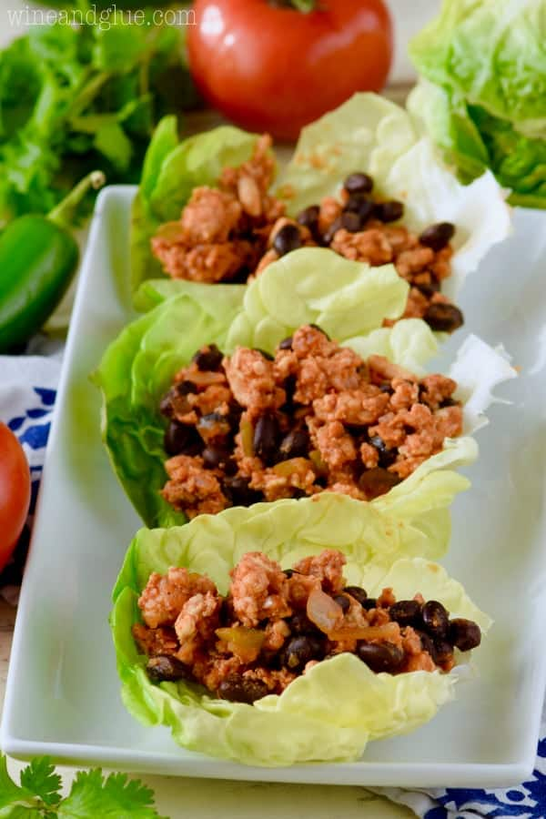 On a white plate, there are three Southwestern Lettuce Wraps filled with a mixture of turkey meat, jalapenos, and black beans.