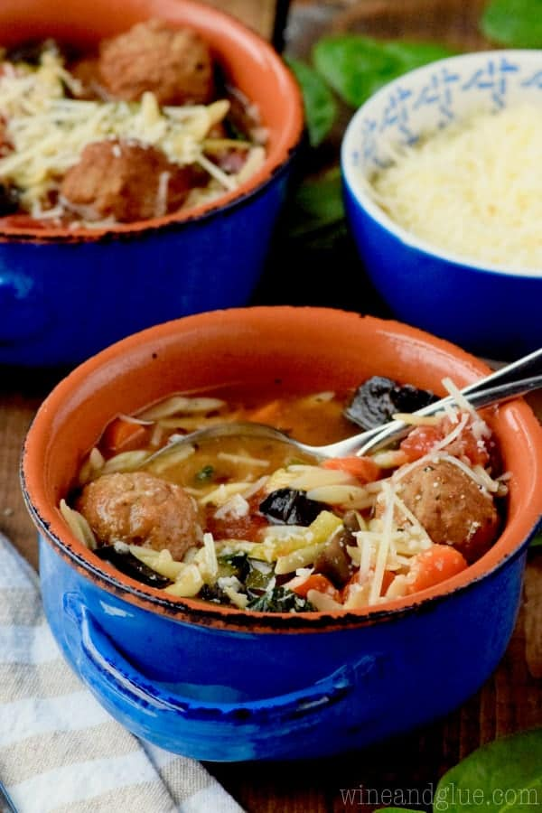 In a blue bowls, the Slow Cooker Vegetable and Meatball Soup is topped with parmesan.
