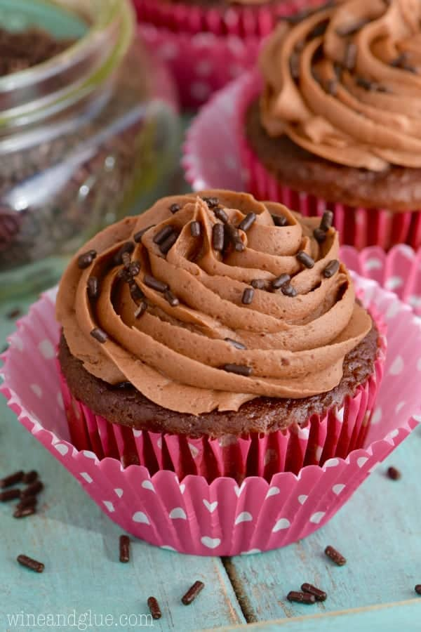 A chocolate muffin in a Valentine's day wrapper has a Chocolate Buttercream Frosting with chocolate sprinkles.