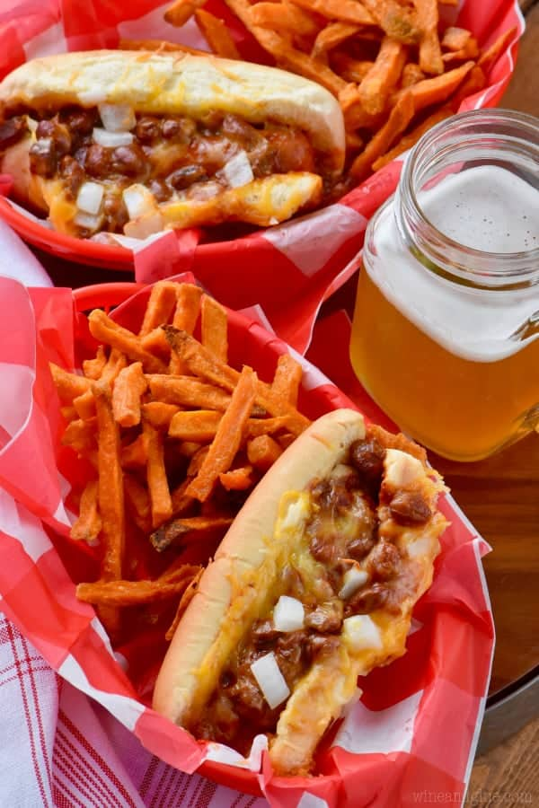 In food baskets, the Oven Baked Chili Cheese Dogs have a side of sweet potato fries and a mason jar full of beer.