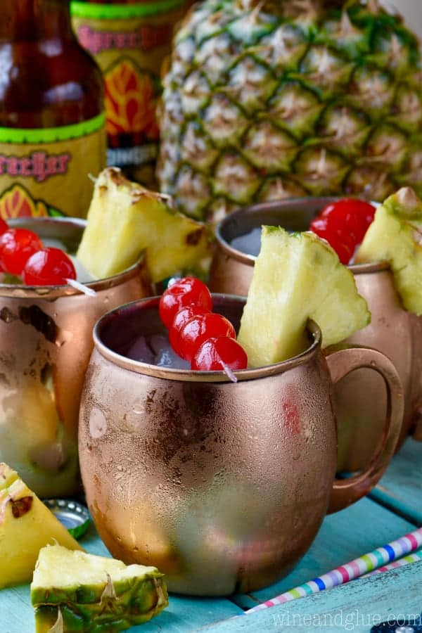 In copper mugs, the Tropical Moscow Mules have ice cubes and on the rim there are sliced pineapples and cherries.