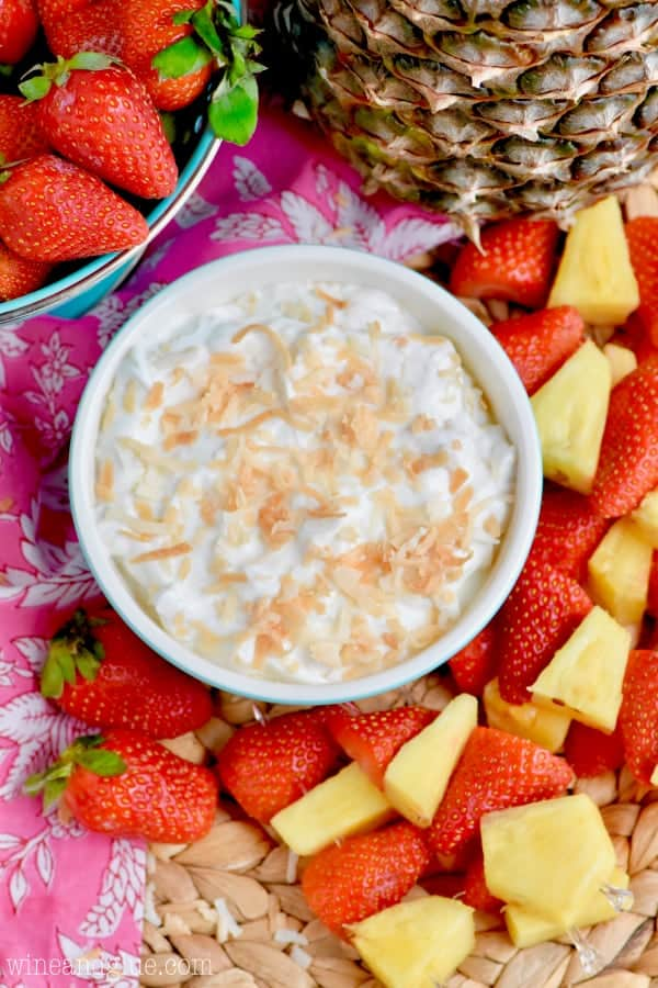 An overhead photo of the Fruit Dip with toasted brown coconut flakes and surrounded by pineapples and strawberries.
