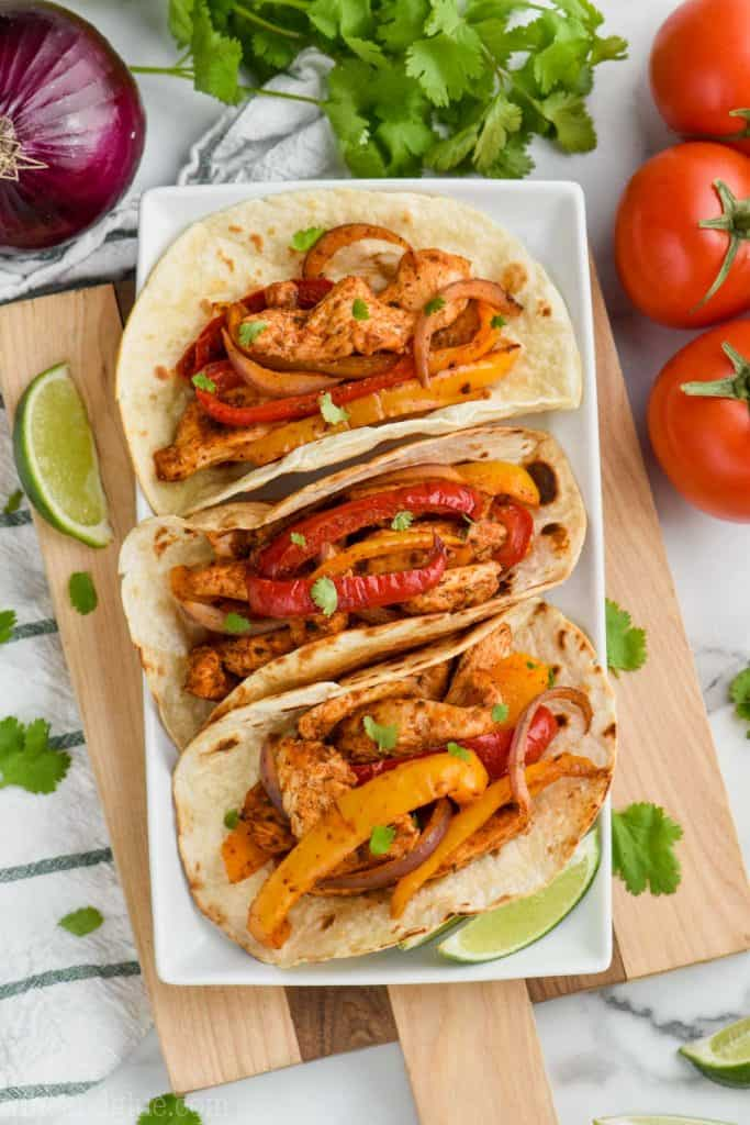 overhead view of three baked chicken fajitas in on a white plate