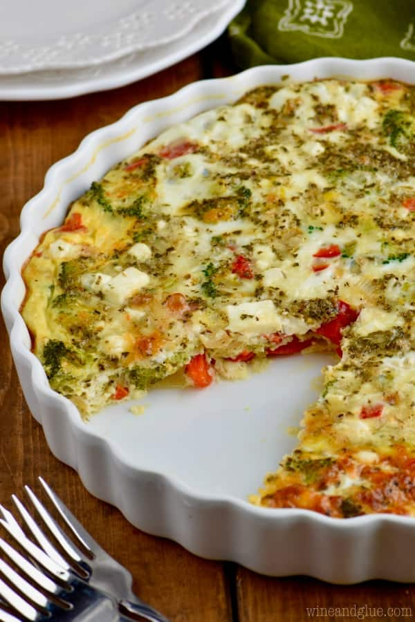 A slice of the Crustless Vegetable Quiche was taken out of the whole quiche showing the the different produce in the quiche.