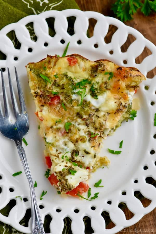On a white plate, a slice of the Crustless Vegetable Quiche has broccoli, red peppers, cheese, and more peaking out.