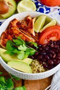 Quinoa taco bowls- Chicken, lime, tomatoes, black beans, avocado quinoa in a bowl garnished with cilantro
