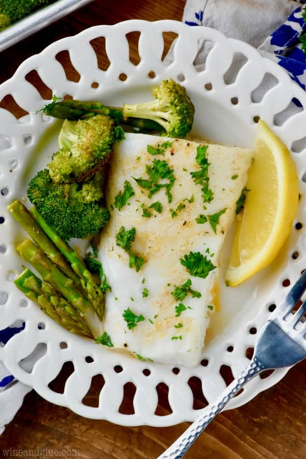 On a white plate, the Baked Cod has a golden brown sear,  topped with parsley, and surrounded with baked asparagus and broccoli.
