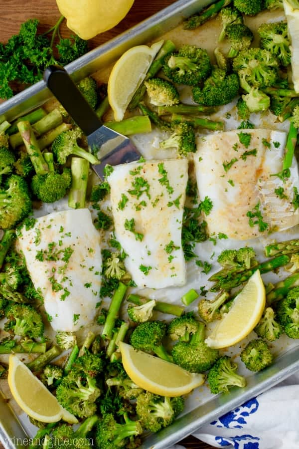 On a sheet pan, three Baked Cods are surrounded by baked asparagus and broccoli