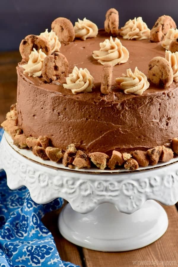 A whole Chocolate Peanut Butter Cookie Cake with a beautiful chocolate frosting. At the bottom of the cake there is crumbled up cookies, and the cake is topped with dollops of peanut butter frosting and cookies.