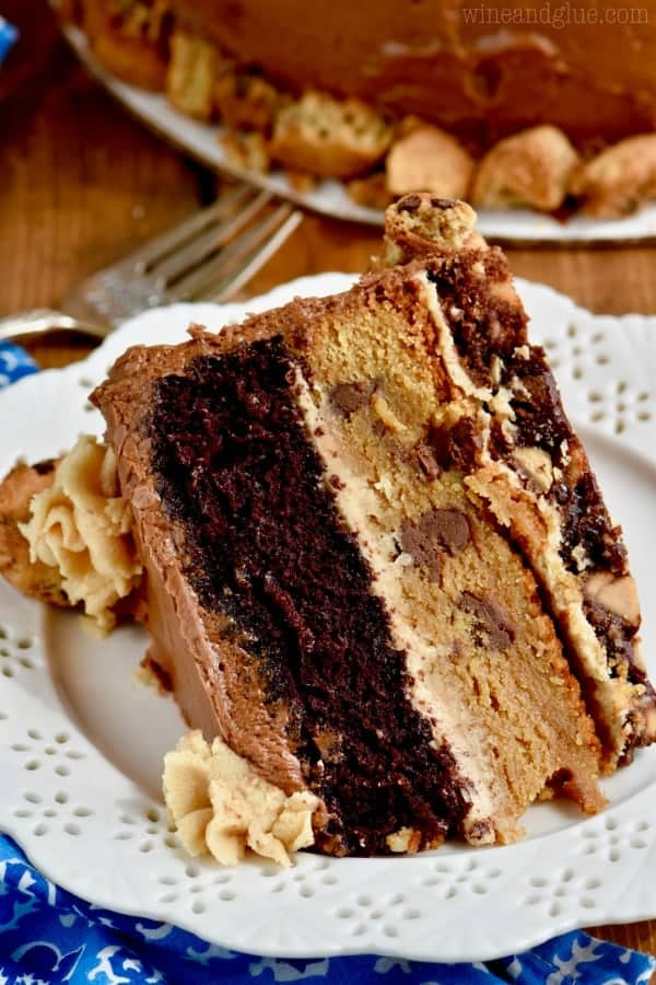 A slice of the Chocolate Peanut Butter Cookie Cake is three layers of brownie, cookie, and chocolate cake with peanut butter and chocolate frosting.