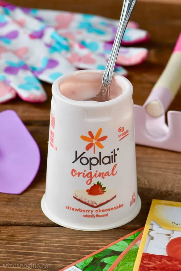 A spoon digging into the Yoplait Original Strawberry Cheesecake.