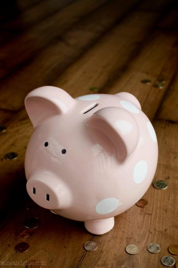 A pink piggy bank surrounded by different coins