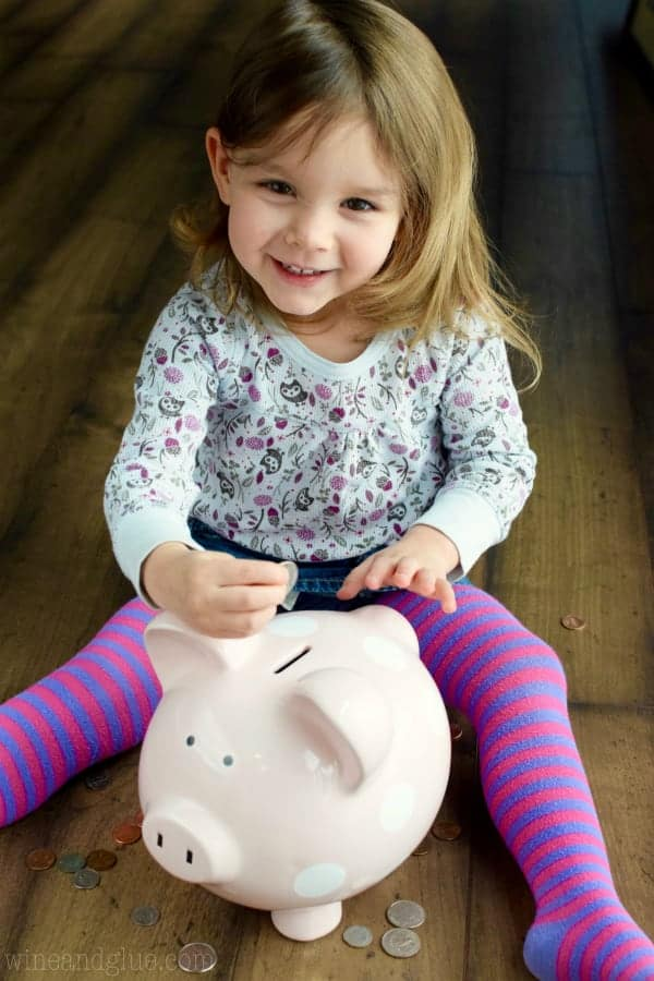 A little girl putting some coins into a pink Piggy Bank