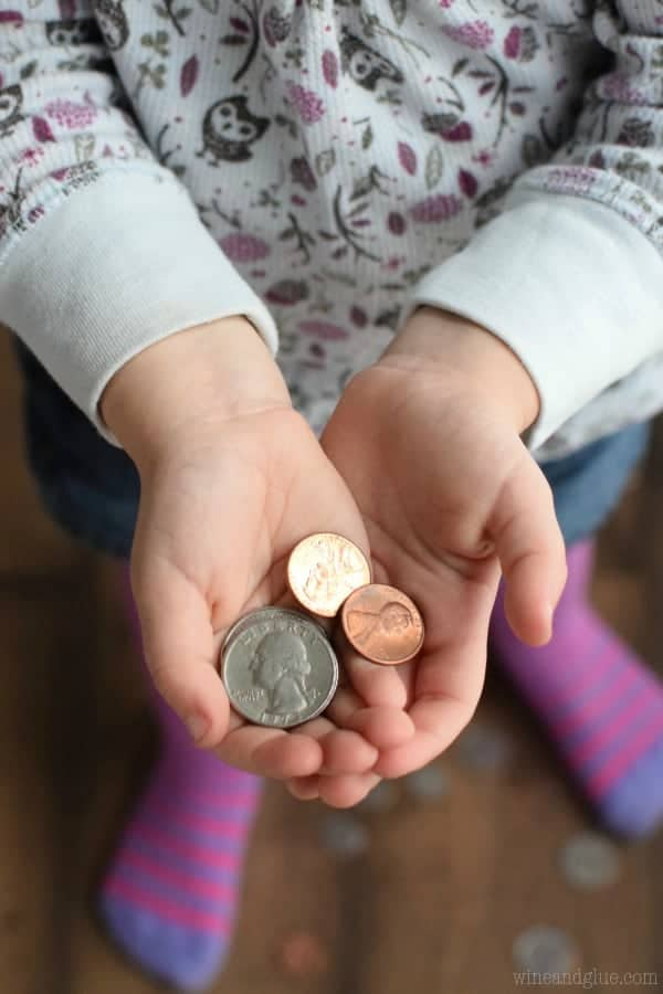 A little girl cupping in her hands some quarters and pennies in her hands.