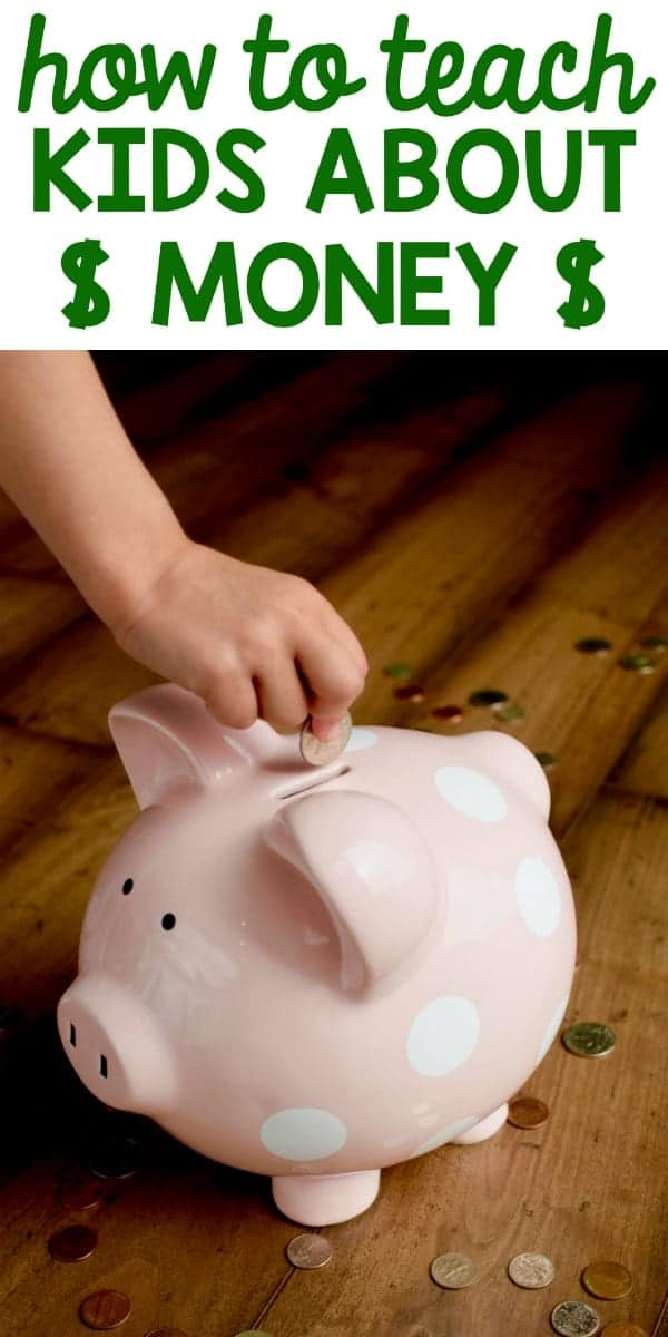 A little girl putting some coins in a pink piggy bank