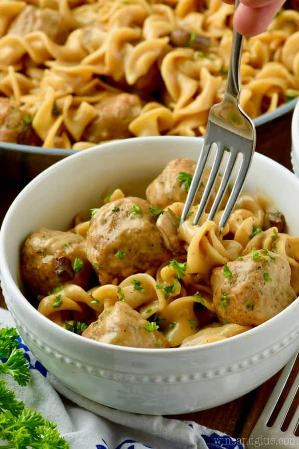 fast and easy stroganoff recipe in a white bowl being forked