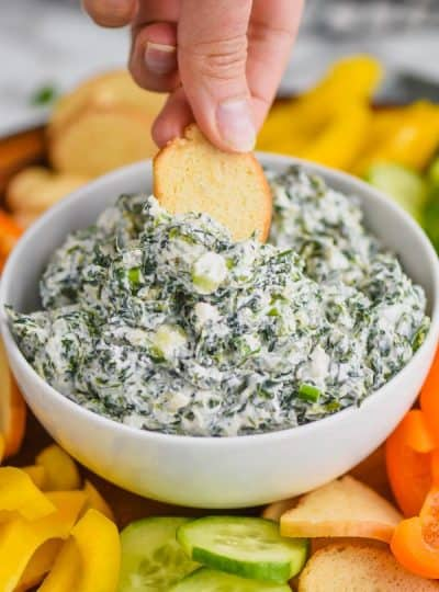 woman dipping a bagel chip into a white bowl full of spinach dip